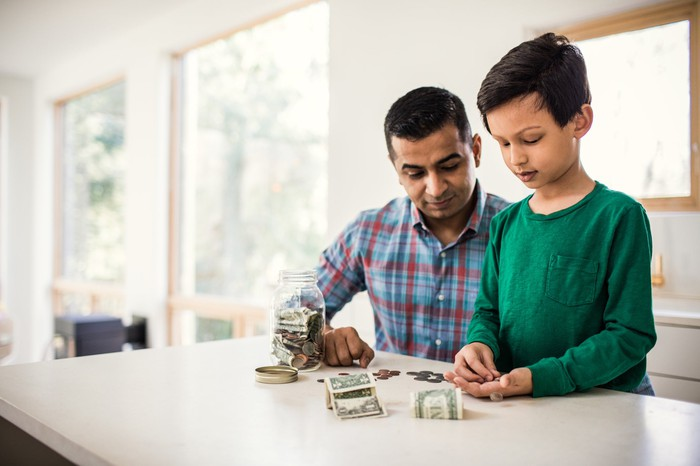 An adult counting dollars and coins with a child.