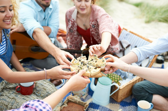 A group of people each taking a piece of a pie at a picnic.