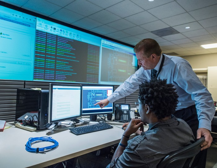 Two colleagues working together in a server control room.