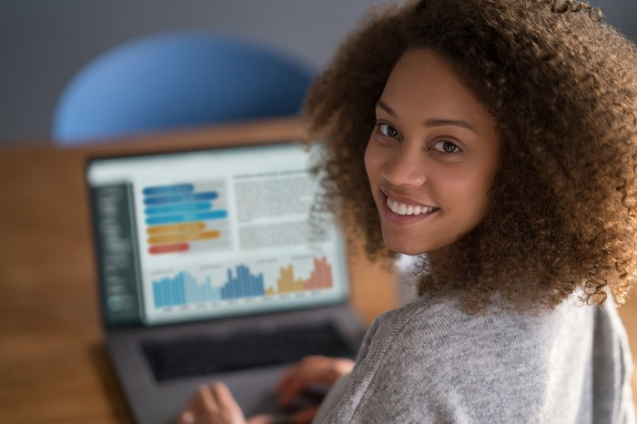 A smiling person working on laptop that shows multiple graphs.