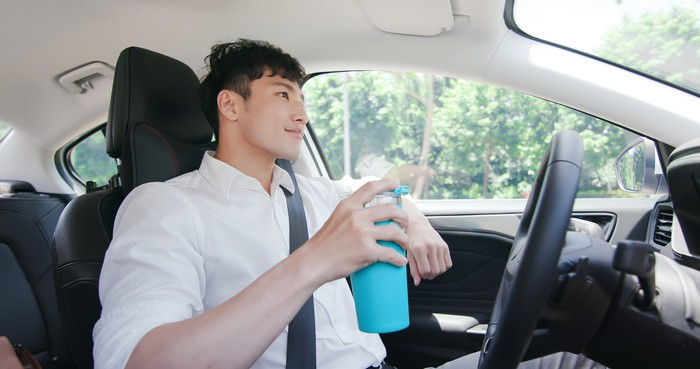 Relaxed person with a mug in their right hand rides in an autonomous self-driving car on road.
