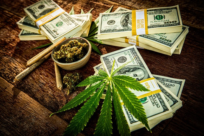 A marijuana leaf and dried flower on a table containing stacks of U.S. currency.