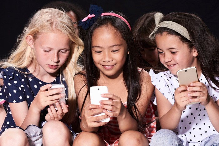 Three children each holding a phone while sharing what they see on social media.