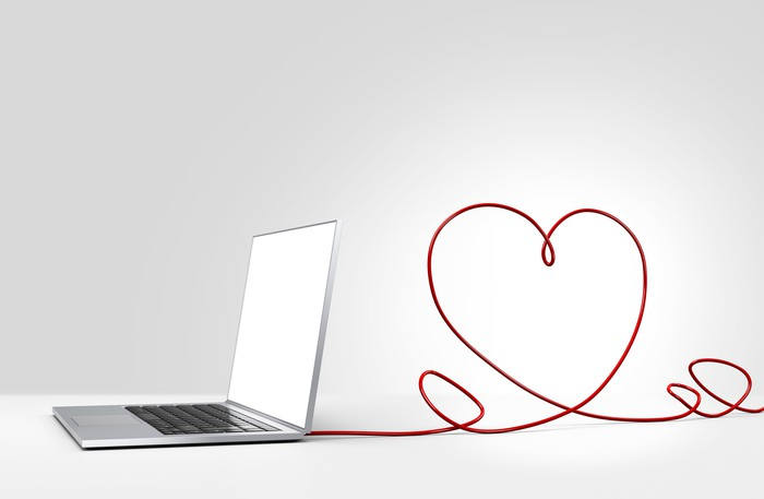 Computer with a string in the shape of a heart attached to it.