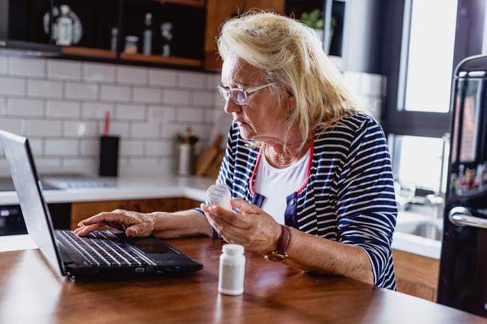 Senior on laptop while reading pill bottle label.