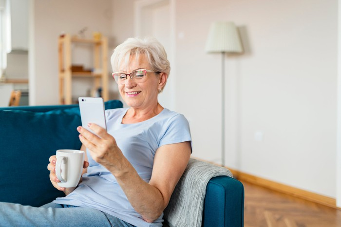 Smiling senior sitting on a couch holding a coffee mug and looking at smartphone.