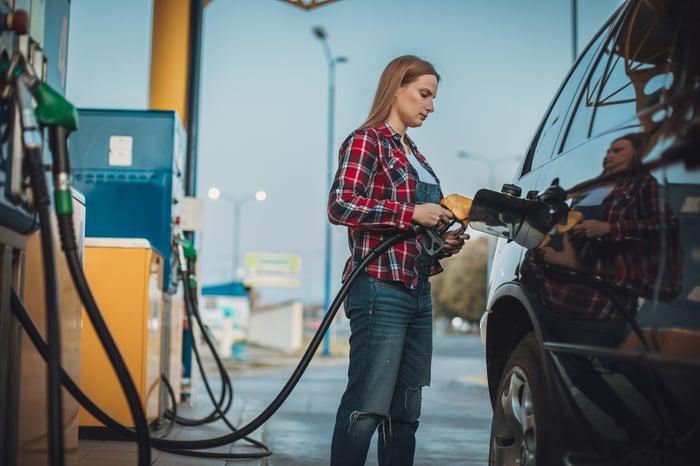 Une personne remplit le réservoir d'essence de sa voiture dans une station-service.