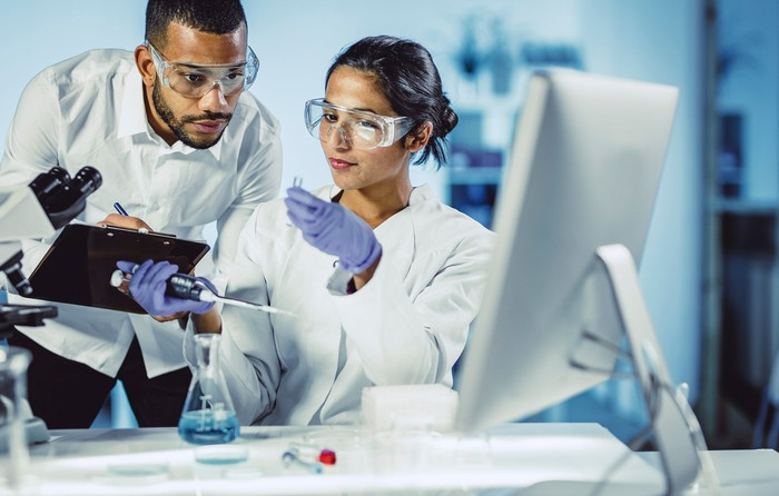 Two lab researchers inspect a sample.