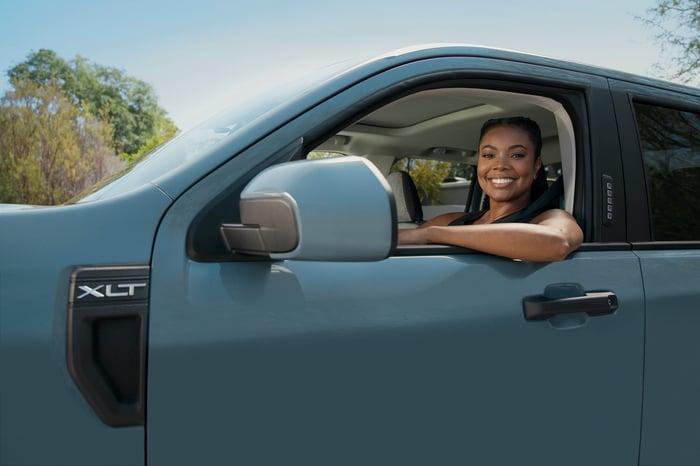 Union est représentée sur le siège conducteur d'une petite camionnette bleue.