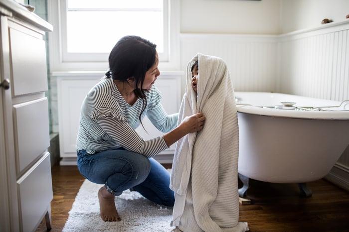 Femme enveloppant un enfant dans une serviette dans une salle de bain.