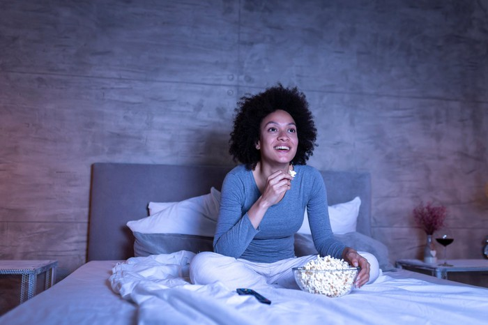 A woman sitting on a bed watching TV.