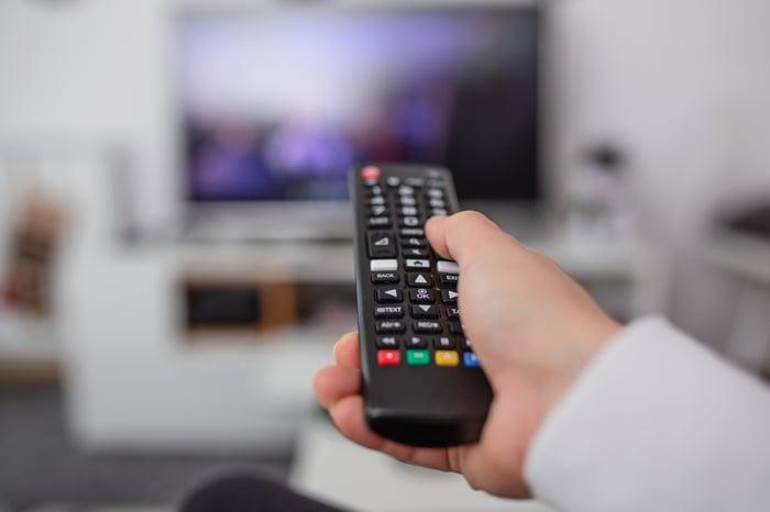 A person holding a TV remote.