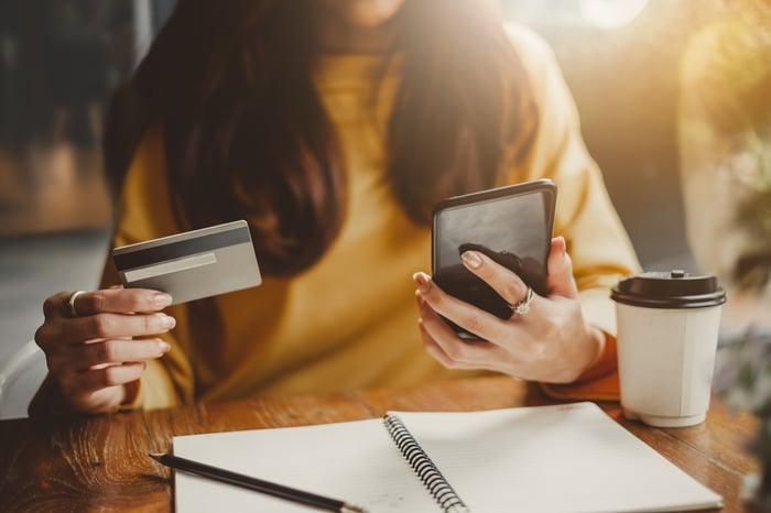Une femme tient un smartphone dans une main et sa carte de crédit dans l'autre.