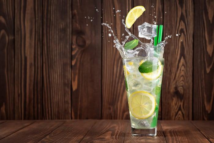 Un verre de limonade avec des glaçons qui tombent dedans.