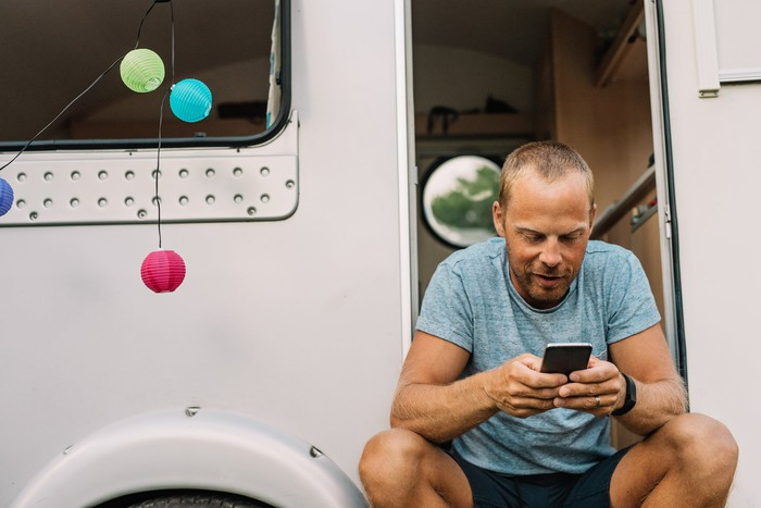 Une personne assise à l'extérieur d'un véhicule récréatif utilisant un téléphone portable.