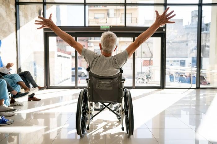 Une personne assise dans un fauteuil roulant, représentée de dos, semble heureuse, les bras tendus.