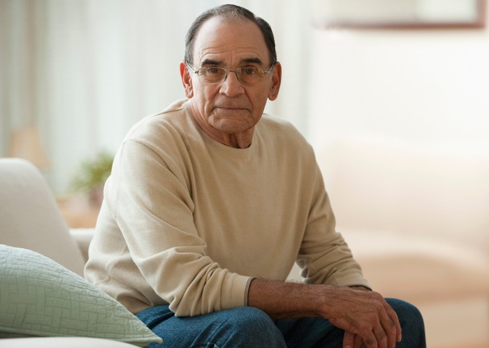 Older person with serious expression sitting on couch.