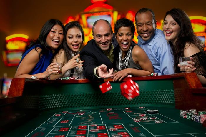 Six personnes heureuses debout autour d'une table de craps dans un casino avec un lancer de dés.