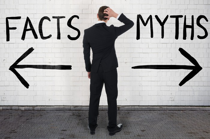 Person looking at opposing signposts reading Facts and Myths.