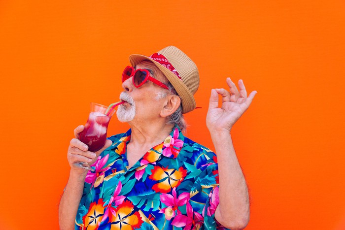 A senior man in a colorful shirt celebrates while sipping a tropical-looking cold drink.