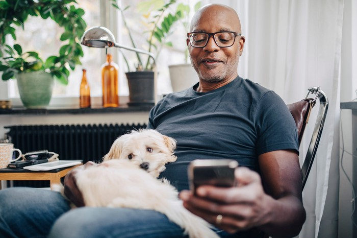 A smartphone user sits with a dog at home.