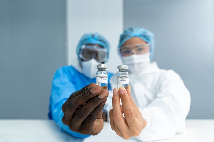 Two researchers hold out vials of coronavirus vaccine.