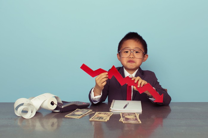 A child in a business suit holds a cutout of a declining chart.