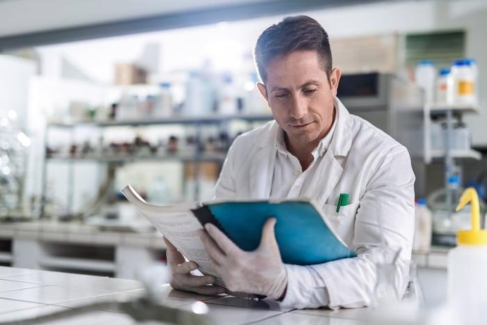 Scientist reading a report in a laboratory.
