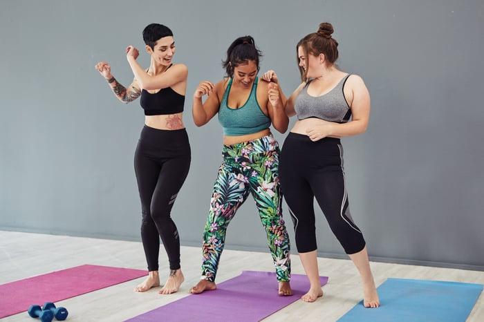 Three happy people standing on yoga mats.