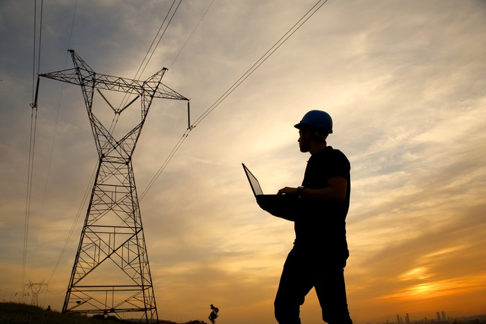 Worker with a laptop examines an electric tower and power lines