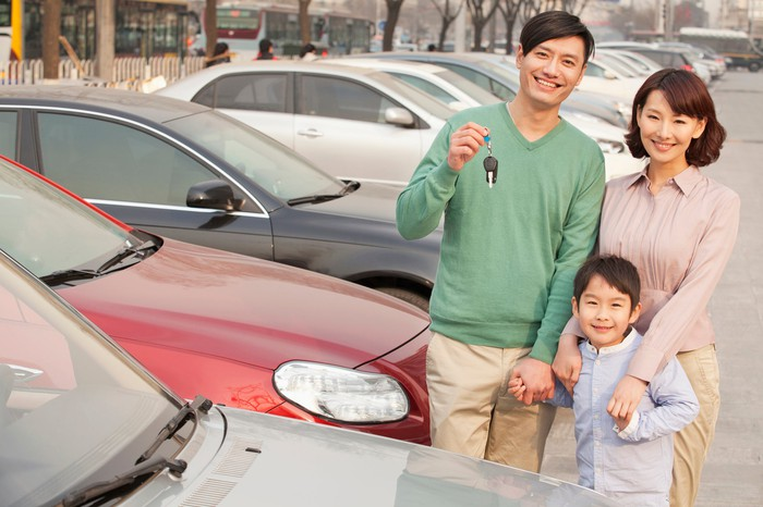 A family stands in the lot of a car dealership.