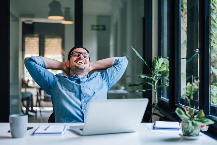 A smiling man sitting at a laptop