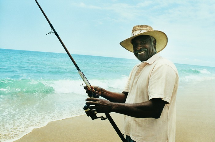 Older person at beach holding fishing rod