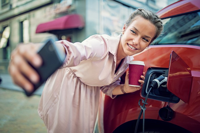 Young lady taking selfie with electric vehicle showing power cord plugged in