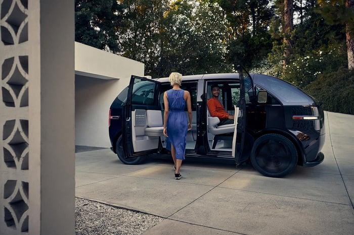 Une personne marchant vers un véhicule Canoo et une autre à l'intérieur.