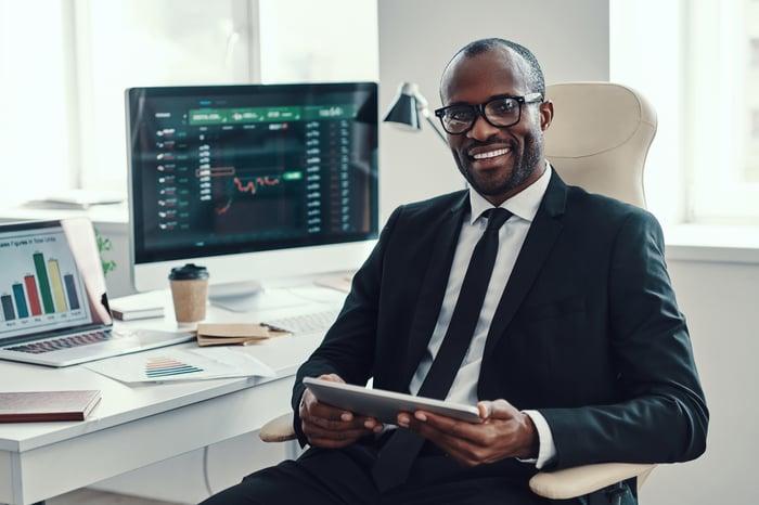 Homme d'affaires tenant une tablette avec des graphiques boursiers sur l'ordinateur portable et l'ordinateur sur le bureau en arrière-plan.