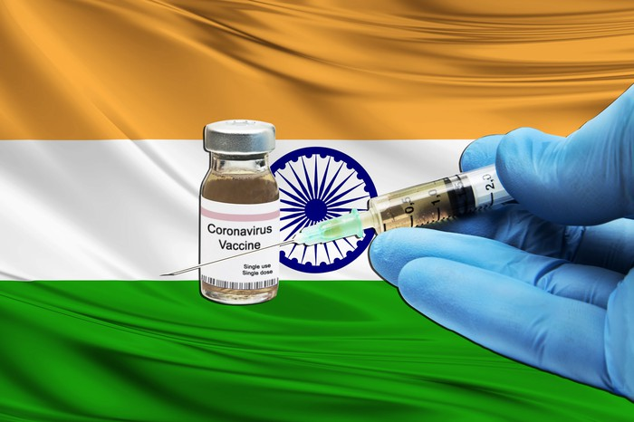 Gloved hands holding a syringe with needle next to a coronavirus vaccine vial with an Indian flag in the background.