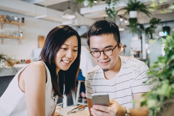 Two smiling people looking at a smartphone.