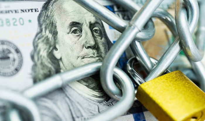 $100 bill with chain and lock.