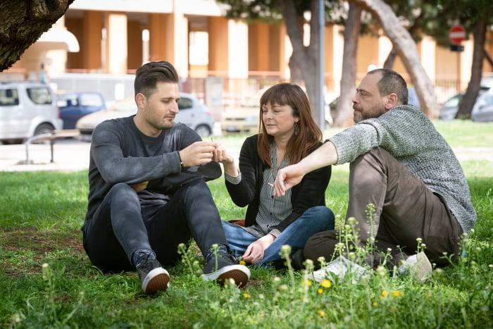 trois amis fumant des joints de marijuana assis sur l'herbe dans un parc.
