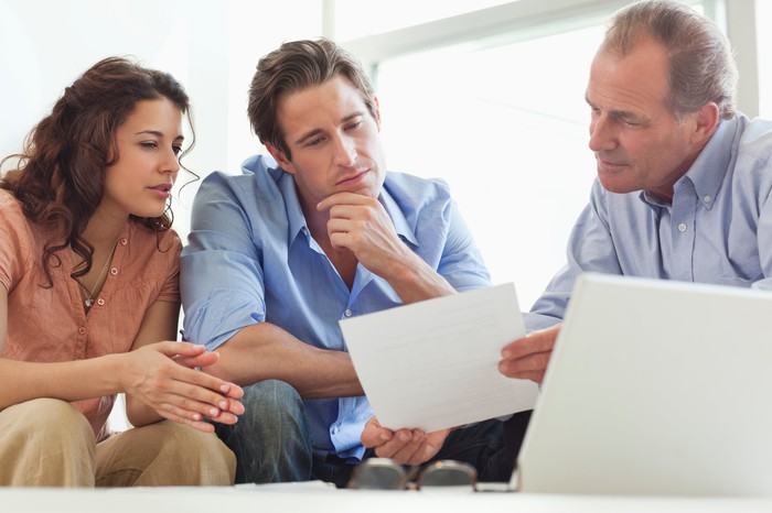 Couple looking at paper with advisor