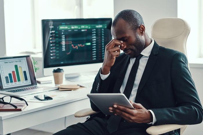 Un investisseur frustré ferme les yeux avec des données boursières affichées autour de lui sur des écrans d'ordinateur.