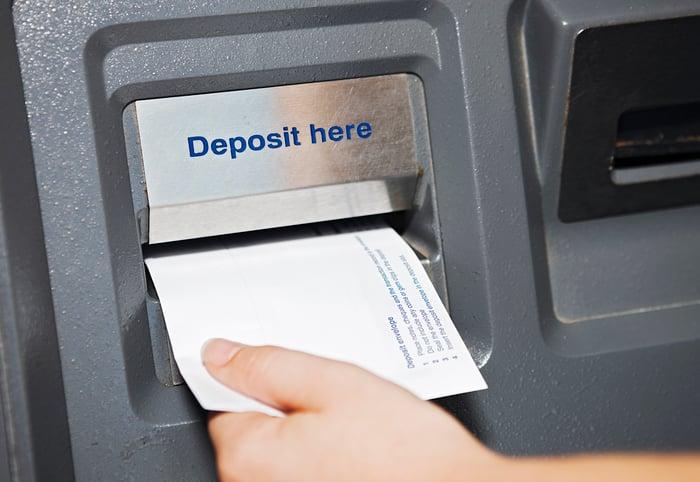 A bank customer makes a deposit.