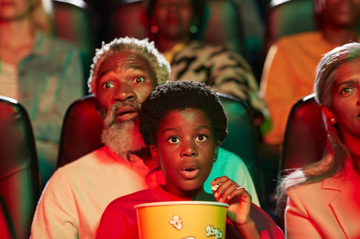 A grandfather and young grandchild on his lap watch a movie in a theater.