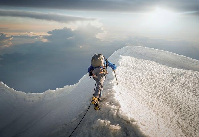 Un hombre sube a una montaña cubierta de nieve.