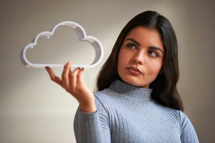 A person holding a cloud icon.