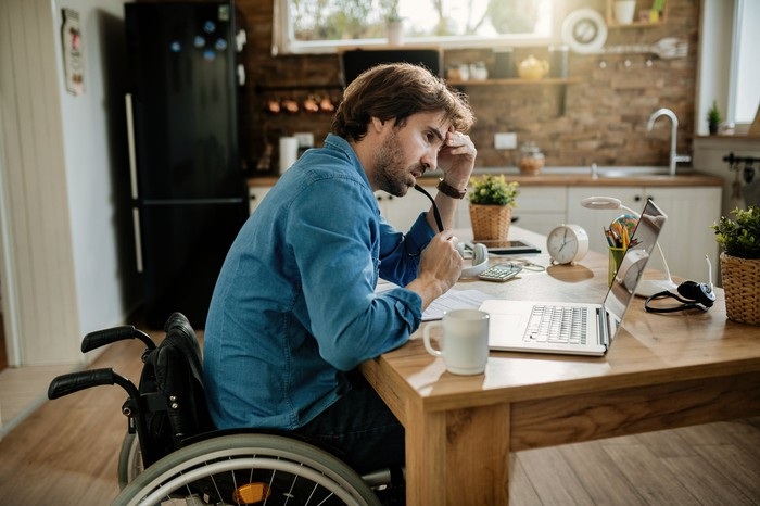 Person who uses a wheelchair seems concerned while looking at laptop.