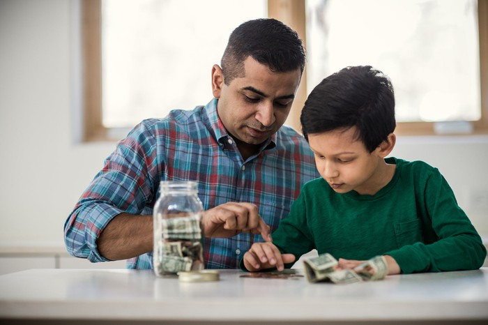 A father and son count out coins on a table.