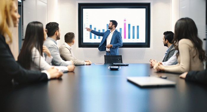 A group of people sit around a conference table looking at one person giving a presentation.