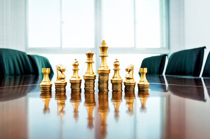 Gold chess pieces stacked on top of coins.